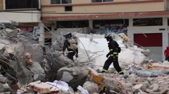 Two fire fighters walking through rubble of collapsed building, 2016 Ecuador Stock Footage