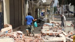 Right pan from a man rolling his bicycle through rubble, Ecuador 2016 quake - stock footage