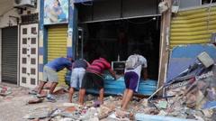 A group of men opening door into their small business, 2016 Ecuador quake Stock Footage