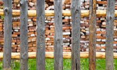 Rustic wooden fence with a cabin beyond - stock photo