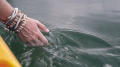 Female hand with bracelets toch water surface Stock Footage