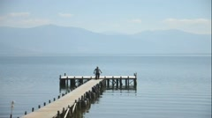 Man and dog on a pier of lake prespa, macedonia Stock Footage