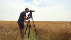 Photographer with tripod on a wheat field - stock footage