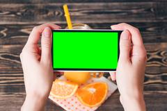 Hands Taking Photo of Oranges. Green Screen. Technology Concept - stock photo