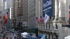 Waving US flags at the building of New York Stock Exchange. First Data. Stock Footage