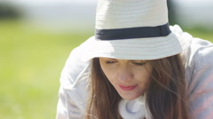 Attractive young woman concentrates as she uses her tablet device outdoors Stock Footage