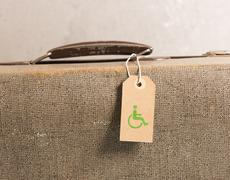 Tag with handicap symbol on old vintage suitcase Stock Photos