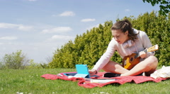Young woman outside using a digital tablet to learn to play her small guitar Stock Footage