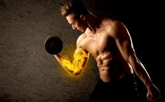 Muscular bodybuilder lifting weight with flaming biceps concept Stock Photos