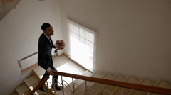 Groom walk upstairs with bouquet Stock Footage