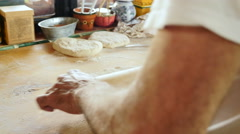 A man uses a rolling pin on a wooden cutting board in his home kitchen Stock Footage