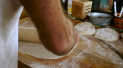 An attractive older man uses a rolling pin to make home made pizza Stock Footage
