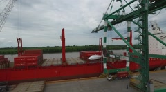 Aerial drone scene flying over an import export harbour in between a huge crane, Stock Footage