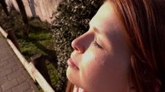Female with eyes closed looking up into sunshine 4k Stock Footage