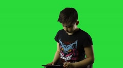 Attractive boy using tablet pc while standing on green chroma key background - stock footage