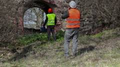 Building inspector talking on smart phone at old ruins before restoration - stock footage