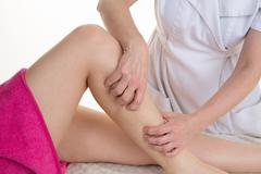 Female osteopath applying pressure with thumb on female calf muscle. Stock Photos
