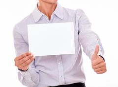 Satisfied businesswoman with a button down shirt, holding a blank signboard w - stock photo