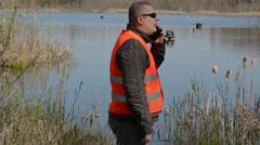 Ornithologist near the duck's houses at the lake Stock Footage