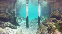 A diver navigates through underwater pilings Stock Footage