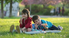 Two little boys having dinner with pizza on sunset, picnic on the grass sprin Stock Footage