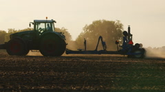 The tractor sows a field at sunset. The sun's rays near the beautiful light Stock Footage