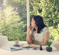 woman working at home while looking out at bright daylight from window - stock photo