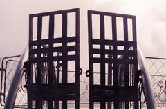 Metal gate with simple decorations sorrounded by misty and foggy spectacular Stock Photos