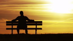 Silhouette man sitting on a bench at sunset, then walks away, in slow motion Stock Footage