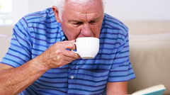 Mature man reading his newspaper and drinking his newspaper Stock Footage