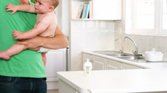 Frustrated father carrying his baby Stock Footage