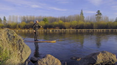 Man paddle boards past the camera Stock Footage