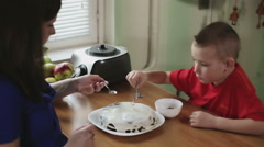 Mother and son putting chocolate on the top of a cake - stock footage