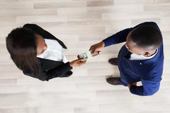 Elevated View Of Business Man And Woman Exchanging Money - stock photo