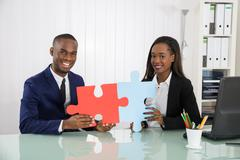 Young Happy Businesspeople Holding Puzzle At Desk And Showing Their Unity Stock Photos
