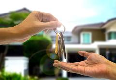 Purchasing  property with two hands and key Stock Photos