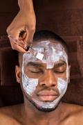 Close-up Of Face Mask Applied To Young Man In Spa - stock photo