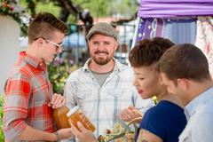 Handsome Man with Honey Vendor at Famers Market Stock Photos