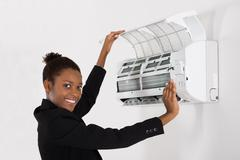 Young Happy African Businesswoman Checking Air Conditioner In Office Stock Photos
