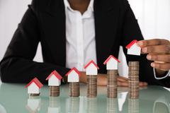 Close-up Of Businesswoman Hand Arranging House Model On Stacked Coins At Desk Stock Photos