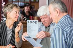 Mature Man Struggles to Read Menu Without Glasses Stock Photos