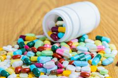 Pill bottle spilling pills on to surface wooden Stock Photos