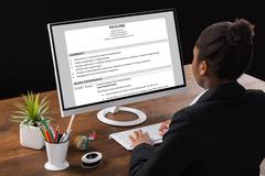 Young African Businesswoman Analyzing Resume On Computer In Office Stock Photos