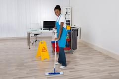 Female Janitor Mopping Wooden Floor With Caution Sign In Office - stock photo
