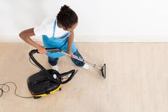 High Angle View Of Young Female Janitor Cleaning Floor With Vacuum Cleaner Stock Photos
