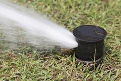 Sprinkler watering in golf course - stock photo