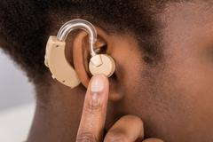 Close-up Of African Woman Wearing Hearing Aid In Ear Stock Photos