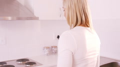 Blonde woman getting dish out oven Stock Footage