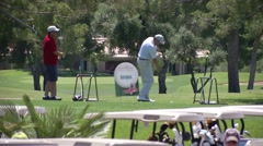 golfer hitting golf ball on golf course - stock footage