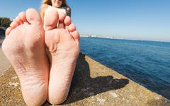 Woman relaxing by seaside showing her dry feet sole - stock photo